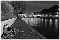Couple sitting on quay on banks of the Seine River. Paris, France ( black and white)