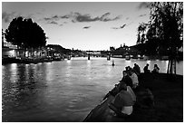 People sitting on tip of Ile de la Cite at sunset. Paris, France ( black and white)