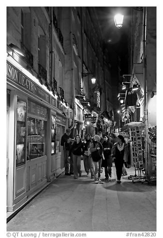 People walking in pedestrian street at night. Quartier Latin, Paris, France (black and white)