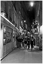 People walking in pedestrian street at night. Quartier Latin, Paris, France ( black and white)