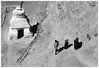 People ascending a trail past a chorten below Phuktal,  Zanskar, Jammu and Kashmir. India ( black and white)