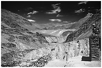 Woman sitting on roof of house in front of mountain landscape, Zanskar, Jammu and Kashmir. India ( black and white)