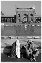 Women sitting near basin in courtyard of Jama Masjid. New Delhi, India (black and white)