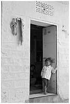 Young boy in doorway of house painted light blue. Jodhpur, Rajasthan, India (black and white)