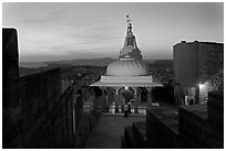 Chamunda Devi temple with man worshipping at sunset, Mehrangarh Fort. Jodhpur, Rajasthan, India (black and white)