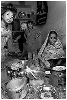Woman cooking, flanked by two girls. Jodhpur, Rajasthan, India (black and white)