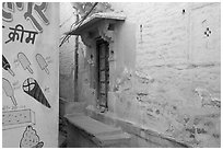 Whitewashed walls with indigo tint and ice-cream depictions. Jodhpur, Rajasthan, India (black and white)