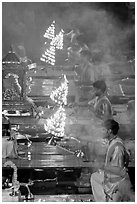 Holy men lifting chandeliers during evening puja. Varanasi, Uttar Pradesh, India (black and white)