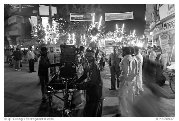 Men pulling generator on bicycle to power lights during wedding procession. Varanasi, Uttar Pradesh, India