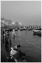 Women soaking clothes in the Ganges River at dawn. Varanasi, Uttar Pradesh, India (black and white)