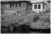 Steps of Manikarnika Ghat with body swathed in cloth and firewood piles. Varanasi, Uttar Pradesh, India ( black and white)