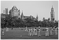 Boys in cricket attire on Oval Maidan, High Court, and Rajabai Tower. Mumbai, Maharashtra, India ( black and white)