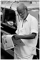 Man reading newspaper next to taxi. Mumbai, Maharashtra, India (black and white)