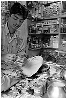 Street vendor preparing a snack with leaves. Mumbai, Maharashtra, India (black and white)