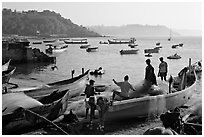 Men repairing net in small fishing boat, early morning, Dona Paula. Goa, India ( black and white)