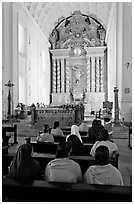 Indian women sitting in front of the altar, Basilica of Bom Jesus, Old Goa. Goa, India ( black and white)