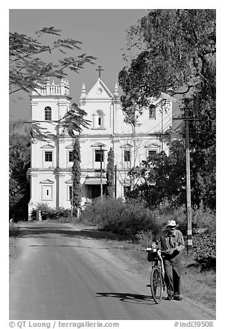 Man walking a bicycle in front of church of St John, Old Goa. Goa, India