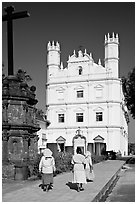 Women walking towards Church of St Francis of Assisi, afternoon, Old Goa. Goa, India ( black and white)