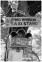 Two wheeler taxi stand and altar on tree. Goa, India (black and white)