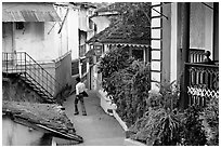 Man in alley with gardens, Panjim. Goa, India (black and white)