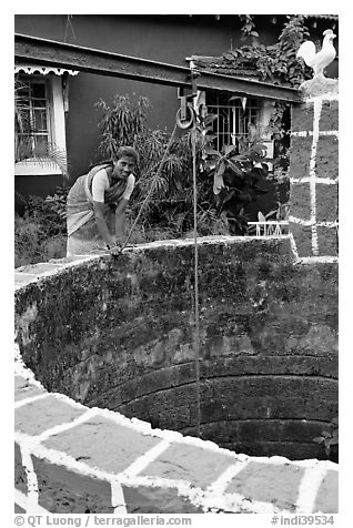 Woman retrieving water from well, Panaji. Goa, India (black and white)