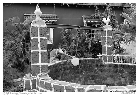 Woman retrieving water from well with blue house behind, Panjim. Goa, India (black and white)