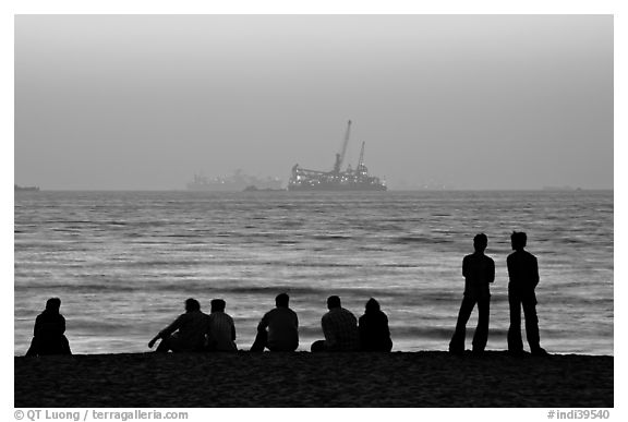 People and  off-shore platforms, Miramar Beach, sunset. Goa, India (black and white)