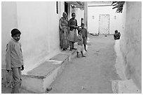 Family in village alley. Khajuraho, Madhya Pradesh, India (black and white)