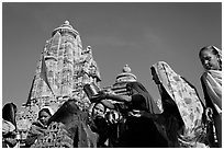 Hindu women making offerings to image with Lakshmana temple behind. Khajuraho, Madhya Pradesh, India (black and white)