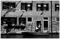 Resident stepping from his boat to his house,  Castello. Venice, Veneto, Italy ( black and white)