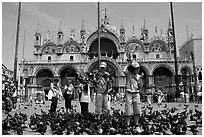 Children feeding flock of pigeon, in front of the Basilica San Marco, mid-day. Venice, Veneto, Italy ( black and white)