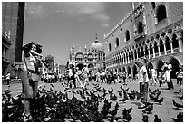 Tourists feeding  pigeons, Piazzetta San Marco (Square Saint Mark), mid-day. Venice, Veneto, Italy ( black and white)