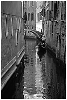 Gondola and reflections in a narrow canal. Venice, Veneto, Italy ( black and white)