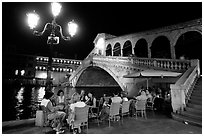 Outdoor cafe terrace,  Rialto Bridge at night. Venice, Veneto, Italy ( black and white)