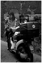 Delivering mail from a scooter. Siena, Tuscany, Italy ( black and white)