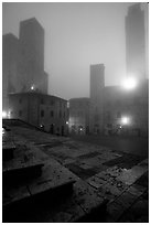 Piazza del Duomo at dawn in the fog. San Gimignano, Tuscany, Italy (black and white)
