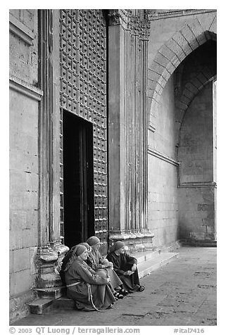 Nuns sit outside of one of  many churches of the historic town. Naples, Campania, Italy (black and white)