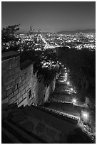Path, wall, and city lights, Suwon Hwaseong Fortress. South Korea (black and white)