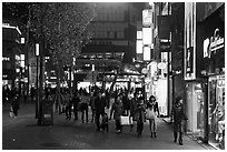 Shoppers strolling on pedestrian street at night. Daegu, South Korea ( black and white)