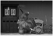 Trishaw, plant and door, Cheong Fatt Tze Mansion. George Town, Penang, Malaysia (black and white)