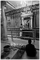Holy man tends to altar, Hindu temple. George Town, Penang, Malaysia ( black and white)