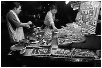 Men arranging skewers on hawker stall. George Town, Penang, Malaysia (black and white)