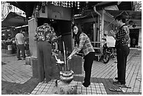 Worshiping at Buddhist street altar. George Town, Penang, Malaysia ( black and white)