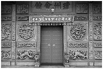 Red door and slate carved wall, Hainan Temple. George Town, Penang, Malaysia ( black and white)