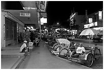 Cycle rickshaws lined on street at night. George Town, Penang, Malaysia (black and white)
