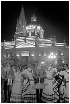 Men and women in traditional mexican costume with Cathedral in background. Guadalajara, Jalisco, Mexico (black and white)