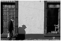 Elderly man walking along a colorful wall, Tlaquepaque. Jalisco, Mexico (black and white)
