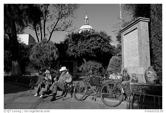 Men sitting in garden, with cathedral dome and ceramic monument, Tlaquepaque. Jalisco, Mexico