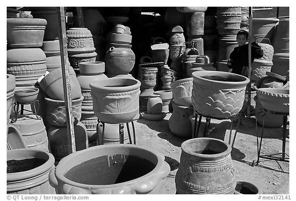 Boy standing next to clay pots, Tonala. Jalisco, Mexico