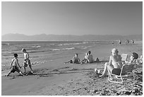 Mothers sitting on beach chairs watching children play in sand, Nuevo Vallarta, Nayarit. Jalisco, Mexico (black and white)